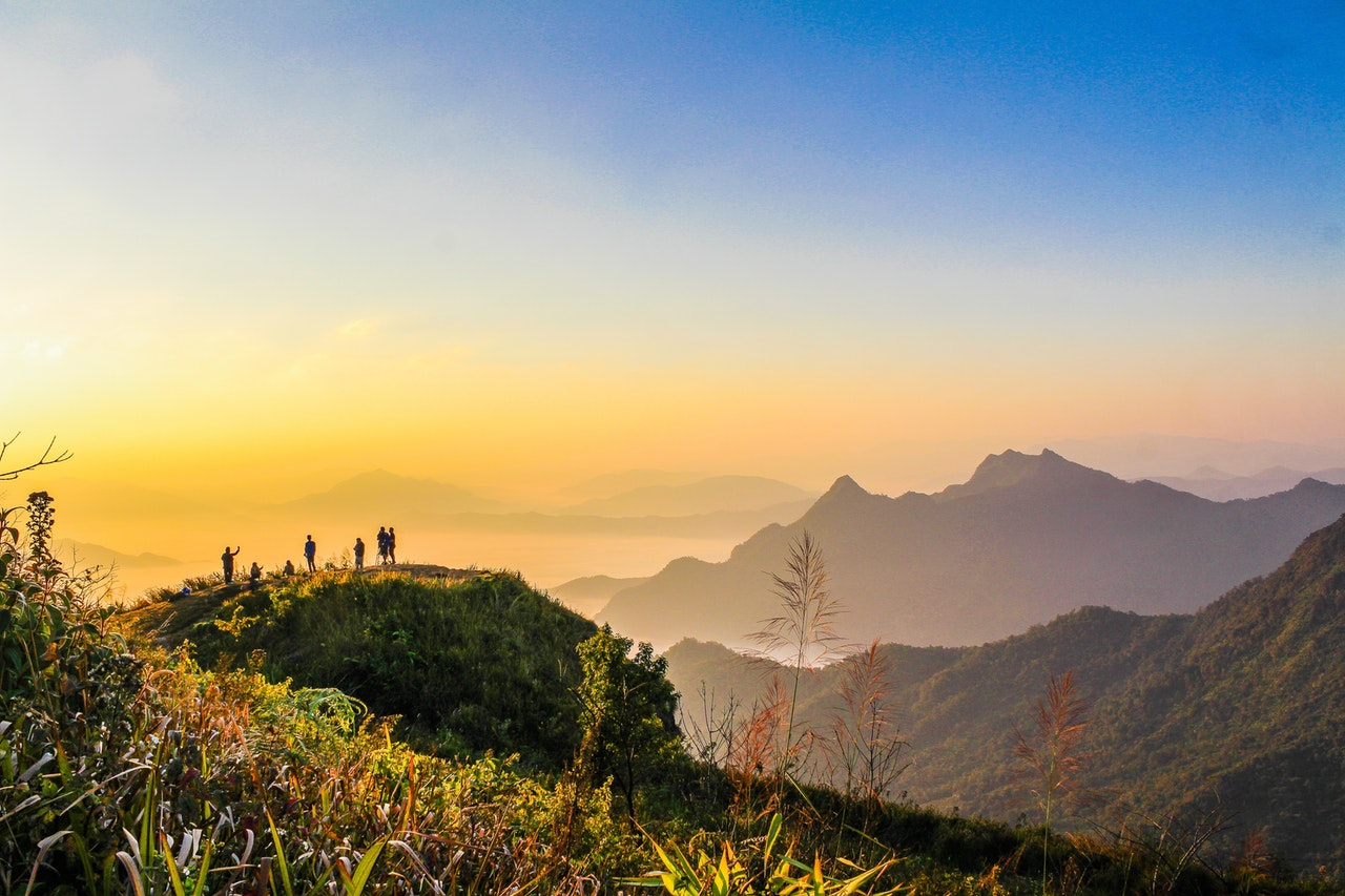 photo-of-people-standing-on-top-of-mountain-near-grasses-733162.jpg